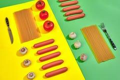 Muitas salsichas cruas com massa e vegetais no fundo verde e amarelo, vista superior Fotos de Stock
