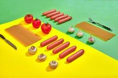 Muitas salsichas cruas com massa e vegetais no fundo verde e amarelo, vista superior Foto de Stock Royalty Free