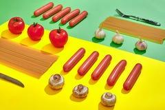 Muitas salsichas cruas com massa e vegetais no fundo verde e amarelo, vista superior Fotografia de Stock Royalty Free