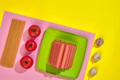 Muitas salsichas cruas na placa No fundo amarelo com massa e vegetais, vista superior Imagem de Stock Royalty Free