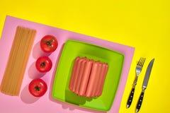 Muitas salsichas cruas na placa No fundo amarelo com massa e vegetais, vista superior Fotografia de Stock Royalty Free