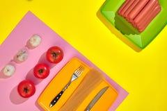 Muitas salsichas cruas na placa No fundo amarelo com massa e vegetais, vista superior Fotografia de Stock