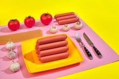 Muitas salsichas cruas na placa No fundo cor-de-rosa e amarelo com massa e vegetais, vista superior Fotografia de Stock