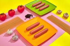 Muitas salsichas cruas na placa No fundo cor-de-rosa e amarelo com massa e vegetais, vista superior Foto de Stock Royalty Free
