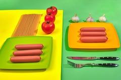 Muitas salsichas cruas na placa No fundo verde e amarelo com massa e vegetais, vista superior Fotos de Stock