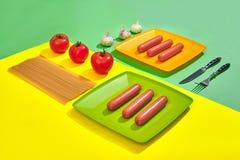Muitas salsichas cruas na placa No fundo verde e amarelo com massa e vegetais, vista superior Fotografia de Stock