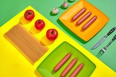 Muitas salsichas cruas na placa No fundo verde e amarelo com massa e vegetais, vista superior Fotografia de Stock Royalty Free