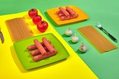 Muitas salsichas cruas na placa No fundo verde e amarelo com massa e vegetais, vista superior Foto de Stock Royalty Free