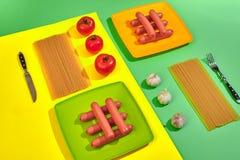 Muitas salsichas cruas na placa No fundo verde e amarelo com massa e vegetais, vista superior Fotos de Stock Royalty Free