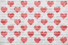 Muitas silhuetas vermelhas do coração em uma parede de tijolo Imagem de Stock