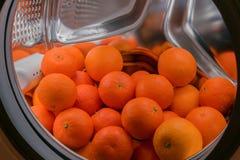 Muitas tangerinas encontram-se no cilindro de uma máquina de lavar Fotografia de Stock Royalty Free