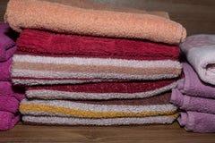 Muitas toalhas coloridas empilhadas no armário Foto de Stock
