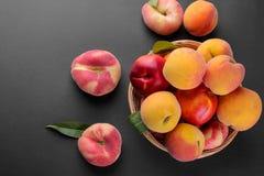 Muitas variedades diferentes de pêssegos em uma cesta de vime em um fundo preto Imagens de Stock