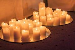 Muitas velas ardentes - luz dos candels na igreja imagens de stock