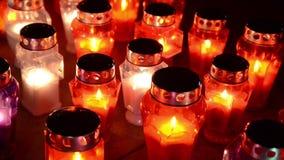 Muitas velas coloridas que queimam-se no cemitério na noite As velas votivas incandescem na sepultura Todo o dia de Saint A oraçã filme