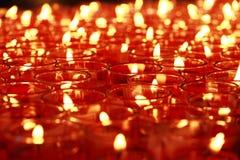 Muitas velas do vermelho que queimam-se no vidro, copo Imagens de Stock
