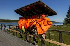 Muitas vestes de vida alaranjadas que penduram perto da estação do barco fotos de stock royalty free
