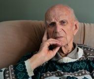 Um ancião que senta-se em uma cadeira Imagens de Stock