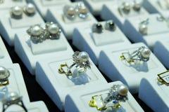Muito anel da prata e de ouro com pérolas e diamante na caixa branca de veludo foto de stock