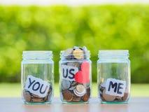 Muito as moedas no dinheiro de vidro rangem na tabela de madeira Imagens de Stock