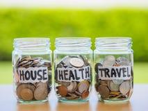 Muito as moedas no dinheiro de vidro rangem na tabela de madeira Imagem de Stock