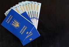 Muito cem dólares e dois passaportes azuis ucranianos Passaporte extrangeiro do ucraniano Corrupção em Ucrânia foto de stock royalty free