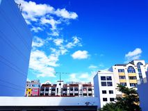 Muito construção colorida, plantas verdes e antena da tevê com céu azul e as nuvens brancas com espaço da cópia imagens de stock