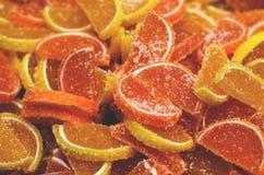Muito doce de fruta sob a forma das fatias alaranjadas no açúcar fotos de stock royalty free