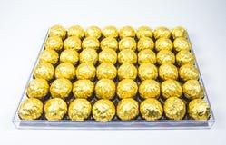 Muito envoltório dourado brilhante do chocolate na linha no fundo branco Fotos de Stock