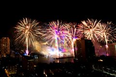 Muito a explosão colorida dos fogos de artifício voa o céu noturno fotografia de stock
