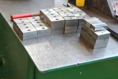 Muito metal brilhante, lingotes quadrados, placas com furos furados, ferramentas do trabajo em metal e apertos industriais na tab fotografia de stock royalty free