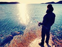 Muito perto vista traseira ao pescador de trabalho Equipe a verificação que introduz a isca e os lances ele distante no mar Foto de Stock Royalty Free