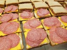 Muito sanduíches da carne e do queijo na cozinha de sopa, alimentando o com fome fotografia de stock