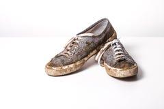 Muito sapatas brancas de Muddy Trainers no branco Fotos de Stock Royalty Free