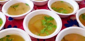 Muito sopa verde quente com as folhas cortadas do portal e da salsa ou do coentro na parte superior na bacia branca foto de stock