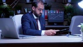 Muito tempo de trabalho do homem de negócios novo na noite video estoque