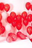 Muitos baloons vermelhos na cama Imagem de Stock Royalty Free