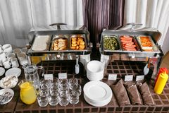 Muitos bofeteiam as bandejas heated prontas para o serviço Café da manhã no bufete da restauração do hotel, recipientes do metal  imagem de stock