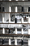 muitos carretéis da linha a girar no tear de tecelagem industrial velho Foto de Stock