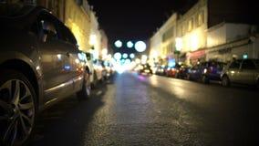 Muitos carros estacionaram ao longo da rua iluminada com lojas, proteção do roubo de carro video estoque