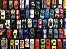 Muitos carros pequenos do brinquedo alinharam na placa foto de stock royalty free