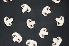 Muitos cogumelos cortaram cogumelos em um fundo preto fotografia de stock