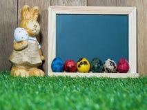 Muitos coloridos dos ovos da páscoa colocados na frente do quadro-negro com coelho da Páscoa Quadro-negro com o colorido dos ovos Fotografia de Stock