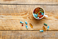 Muitos comprimidos coloridos no copo wodden sobre a tabela Imagem de Stock