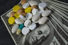 Muitos comprimidos sobre em uma pilha dos dólares Fotografia de Stock
