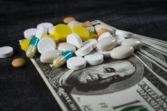 Muitos comprimidos sobre em uma pilha dos dólares Fotos de Stock Royalty Free