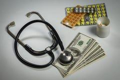 Muitos comprimidos, um estetoscópio e dinheiro em uma tabela Imagem de Stock Royalty Free
