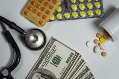 Muitos comprimidos, um estetoscópio e dinheiro em uma tabela Fotografia de Stock