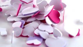Muitos confetes cor-de-rosa do coração que deixam cair no assoalho vídeos de arquivo