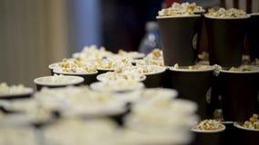 Muitos copos da pipoca no cinema a??o Pipoca fresca perfumada deliciosa cozinhada antes do filme no cinema Noite dentro filme